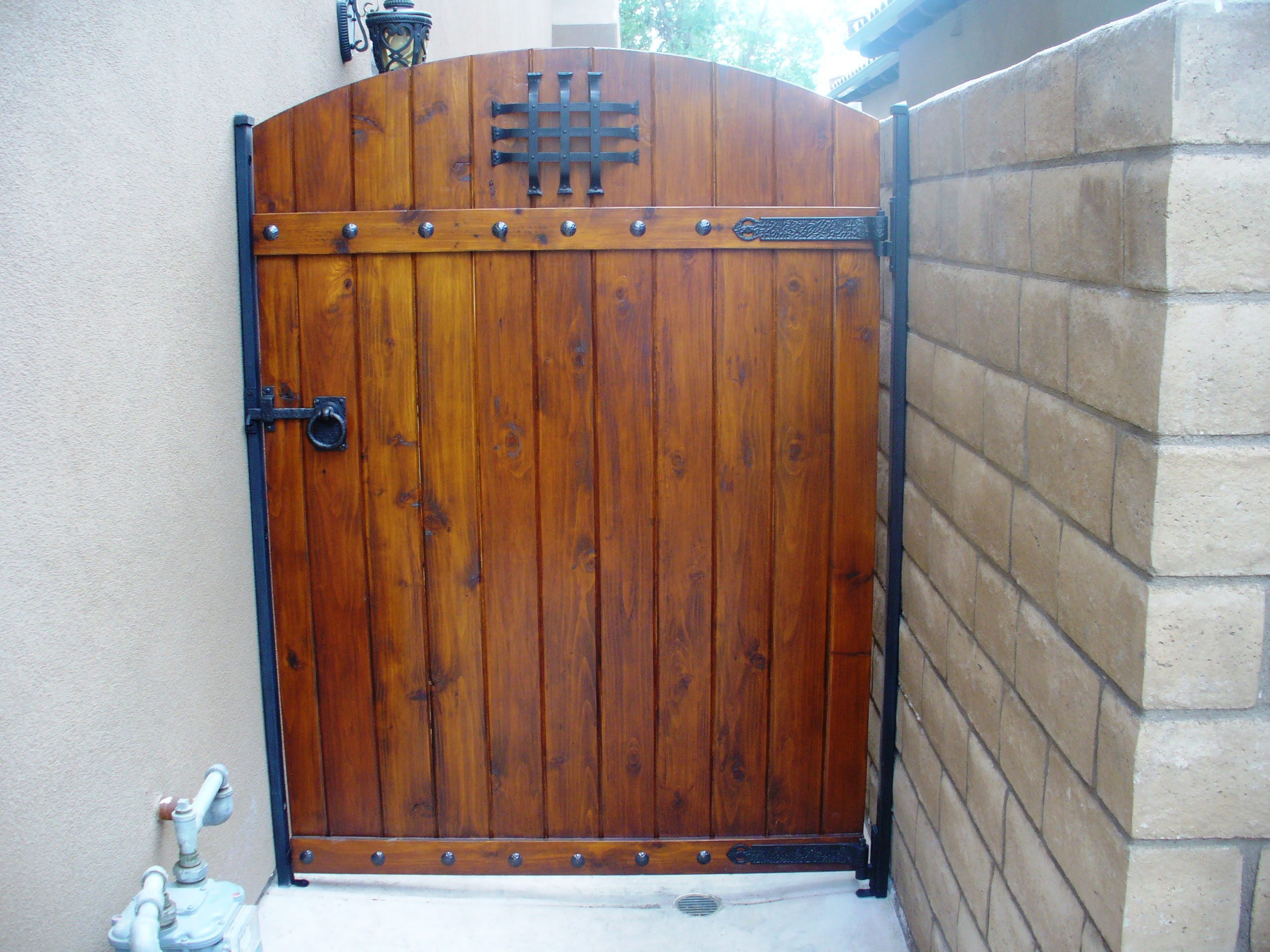 Pedestrian side gate with gate designs including a speak easy, ring pull / lever, clavos and strap hinges.