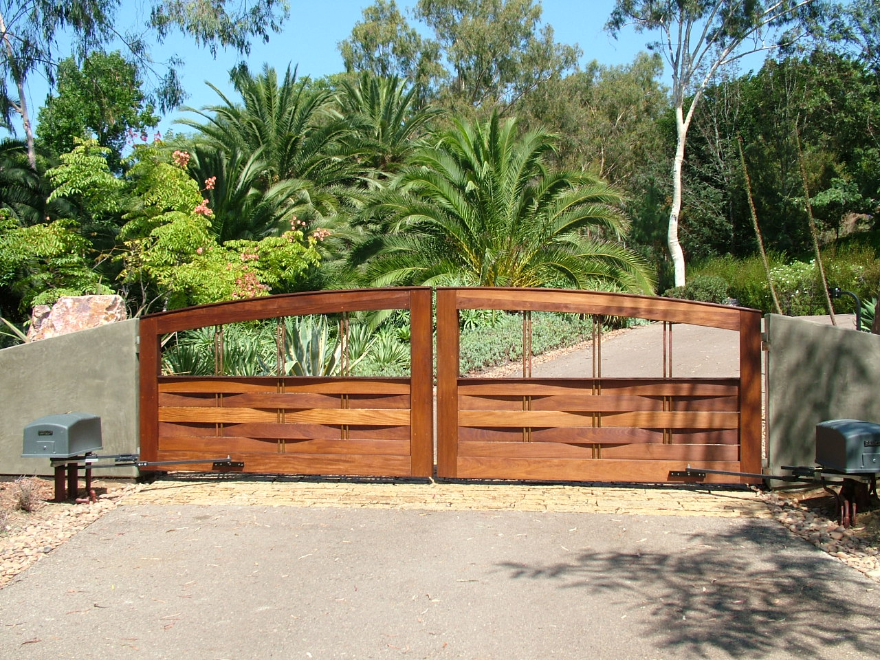 A very natural looking wood gate, a contemporary wall.  Great combination of gate designs.